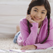 Stock Photo: Young Hispanic girl doing homework on the floor