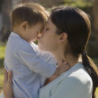 Hispanic mother kissing baby outdoors — Stock Photo