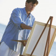 Man painting on easel outdoors - Stock Photo