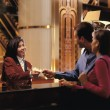 Female receptionist giving room key to couple — Stock Photo