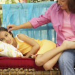 Stock Photo: Hispanic mother and daughter on bench outdoors