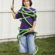 Mixed Race boy wrapped in garden hose — Stock Photo
