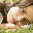 Close up portrait of woman laying in grass — Stock Photo