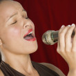 Woman singing into microphone with eyes closed — Stock Photo #13228079