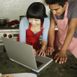 Couple in kitchen using laptop — Stock Photo #13228087