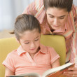 Mother looking over shoulder of daughter who is reading — Stock Photo