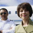 Stock Photo: Businesswoman and male pilot standing in front of private airplane