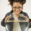 Photo: Young girl holding a fishbowl