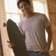 Young African man holding skateboard — Stockfoto