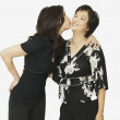 Studio shot of adult Asian daughter kissing mother on cheek — Stock Photo