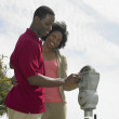 African couple putting coins in parking meter — Stock Photo