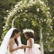 Stock Photo: Hispanic bride and young girl smiling at each other