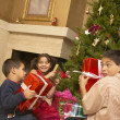 Hispanic siblings shaking Christmas gifts — Stock Photo #13228230