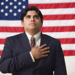 Businessman standing in front of an American flag with one hand across his heart — Stock Photo #13228233