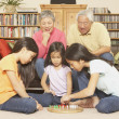 Three young Asian sisters playing chinese checkers while grandparents watch — Stock Photo