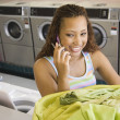 Woman talking on phone with basket of laundry in laundromat - Stock Photo
