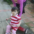 Hispanic mother helping young daughter ride tricycle — Stock Photo #13228265