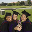 Female graduates taking self portrait - Stock Photo