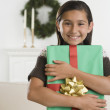Hispanic girl holding gift and smiling — Stock Photo #13228318
