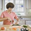 Senior Asian woman chopping vegetables — Stock Photo