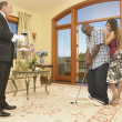 Couple playing golf in house with servant watching - Foto de Stock