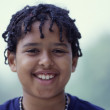 Stock Photo: Close up portrait of boy with dread locks smiling