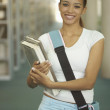 Young woman carrying books and bag — Stock Photo