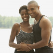 African couple smiling and hugging outdoors — Stock Photo