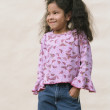 Little girl standing with hands in pockets — Stock Photo