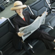 Woman reading newspaper at airport - Stock Photo