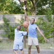Stock Photo: Father and son playing basketball