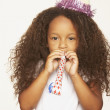 African girl wearing party hat and blowing noise maker — Stock Photo