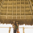Foto Stock: Couple standing underneath thatch roof