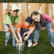 Mixed Race children painting fence — Stock Photo #13228442