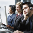 Three businesspeople talking on headsets — Stock Photo