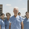 Group of doctors smiling in urban setting — Stock Photo