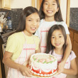Three young Asian sisters holding a cake in the kitchen  — Stock Photo