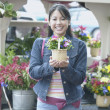 Asian woman holding potted plant — Stock Photo