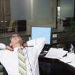 Businessman stretching at desk — Stock Photo