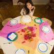 Hispanic girl sitting alone at birthday party - Stockfoto