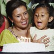 Young girl blowing out the candles on her birthday cake — Stock Photo #13228644