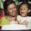 Young girl blowing out the candles on her birthday cake — Stock Photo
