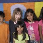 Multi-ethnic children in front of mural — Stock Photo