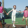 Three girls playing in park while holding hands - Stock Photo