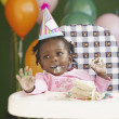 African baby in high chair wearing party hat and eating cake — Stock Photo