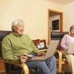 Senior Asian couple having tea while using laptops — Stock Photo #13228671