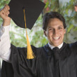 College graduate wearing cap and gown — Stock Photo