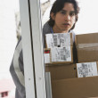 Royalty-Free Stock Photo: Male delivery person with stack of boxes