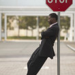 Businessman leaning against stop sign — Stock Photo