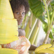 Portrait of woman in banana tree holding bananas — Stock Photo